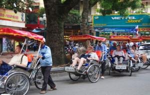 Touristen werden mit Fahrradrikschas um den Hoan Kiem See gefahren